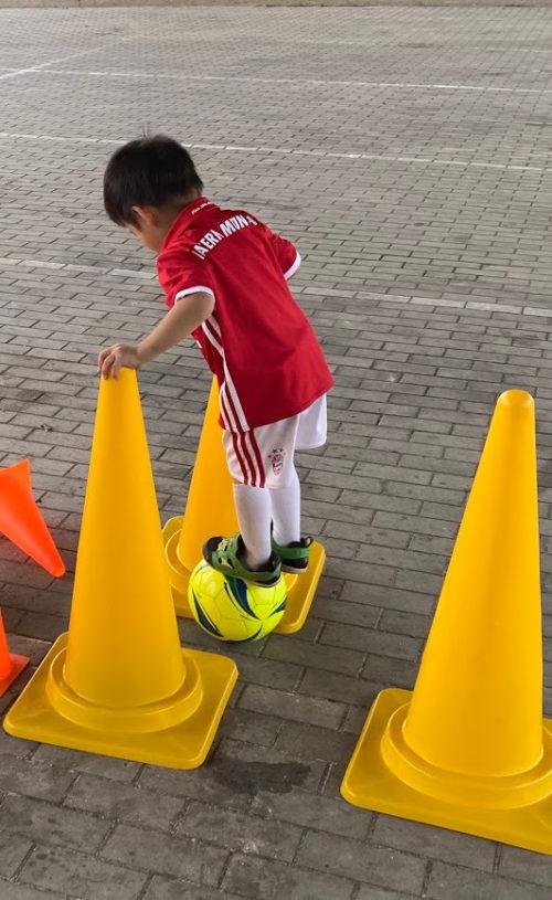 サッカーボールに乗る子ども