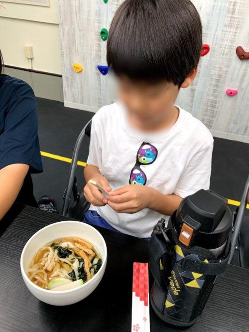 粉から作ったうどんを食べる子ども