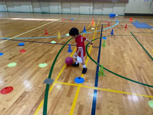 体育館でボールを蹴る子ども