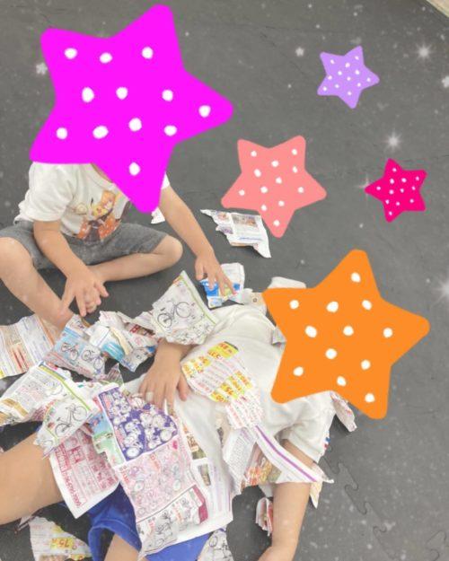 新聞紙の布団で寝る子ども